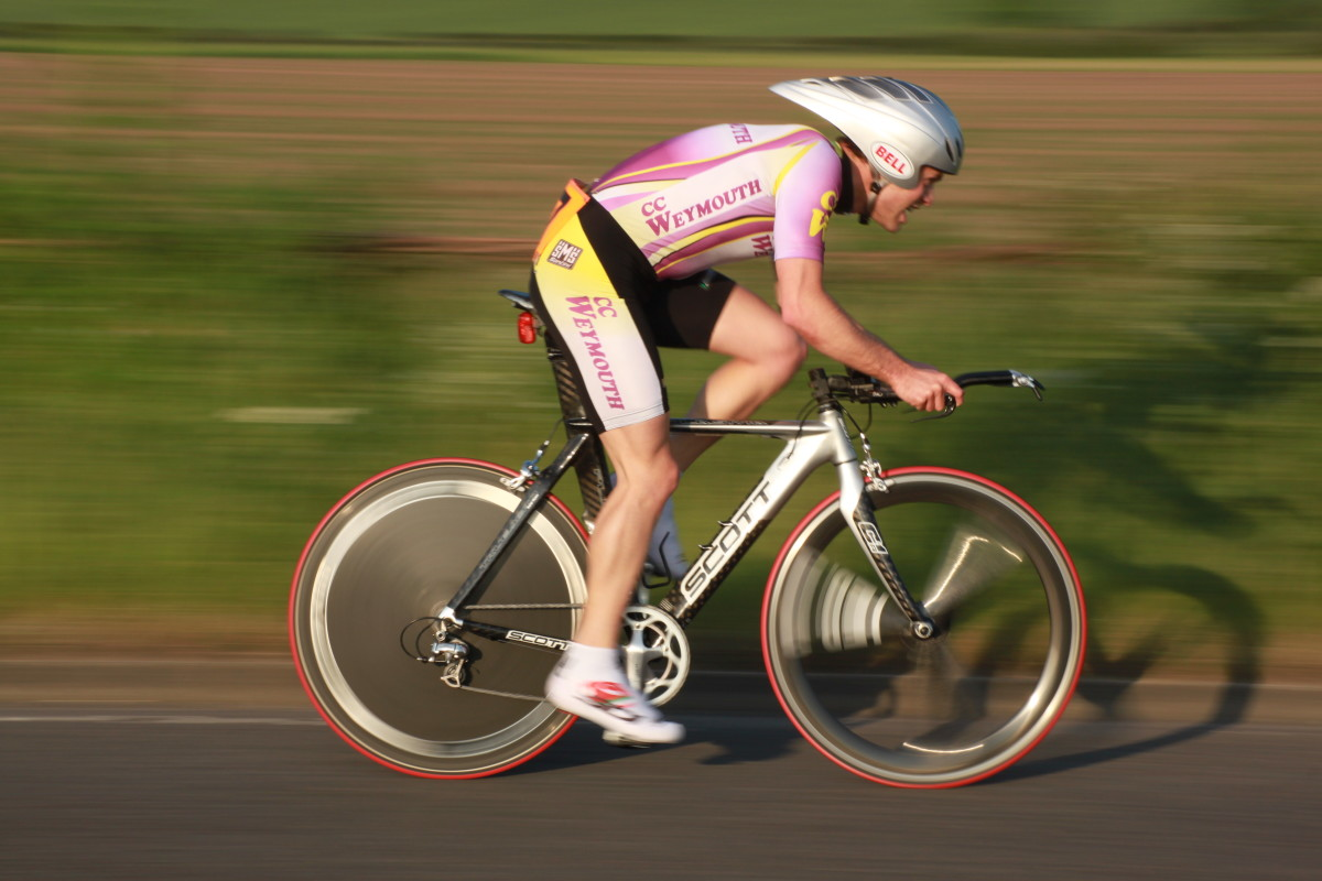 An erodynamic helmet, time trial bicycle, and aerodynamic wheelset with a rear disc can help you ride a faster time trial. Bike pictured is a Scott Plasma with a fron HED tri-spoke carbon wheel and disc wheel to cut through the air