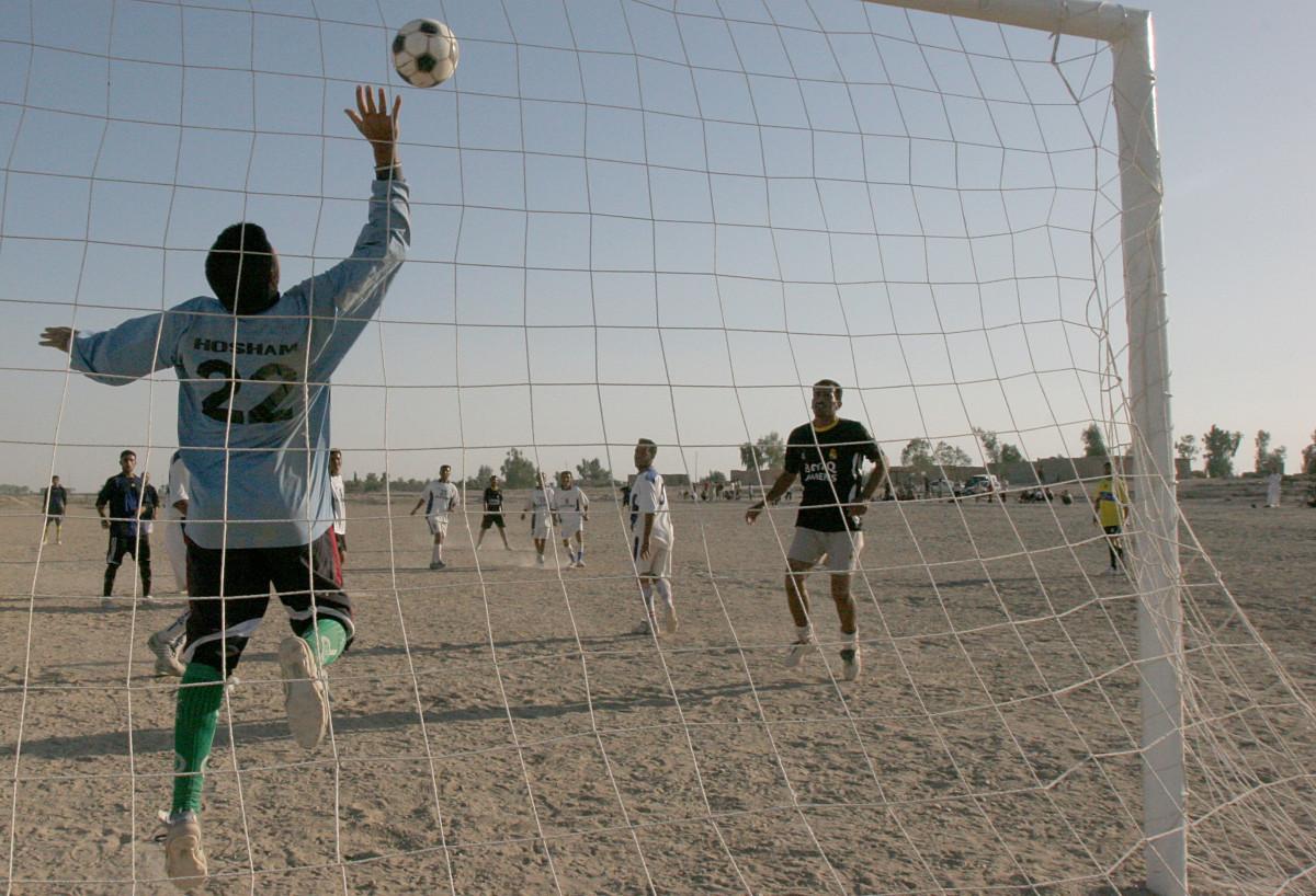 A goalkeeper jumping up to block an attempt at scoring.