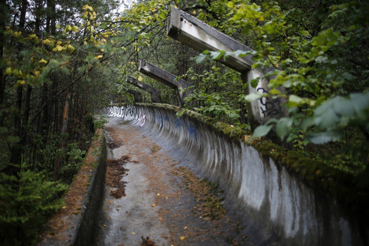 The bobsled run now overgrown with plants.