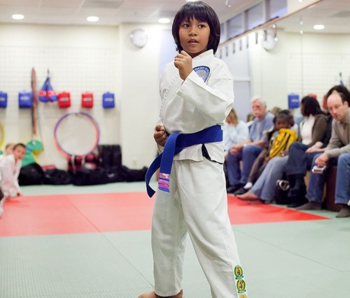 A young woman with a blue belt testing for purple.