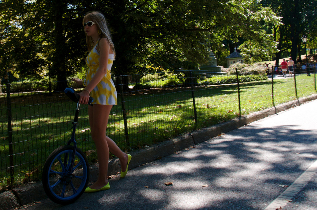 A young unicyclist enjoying an afternoon in Central Park, New York City.