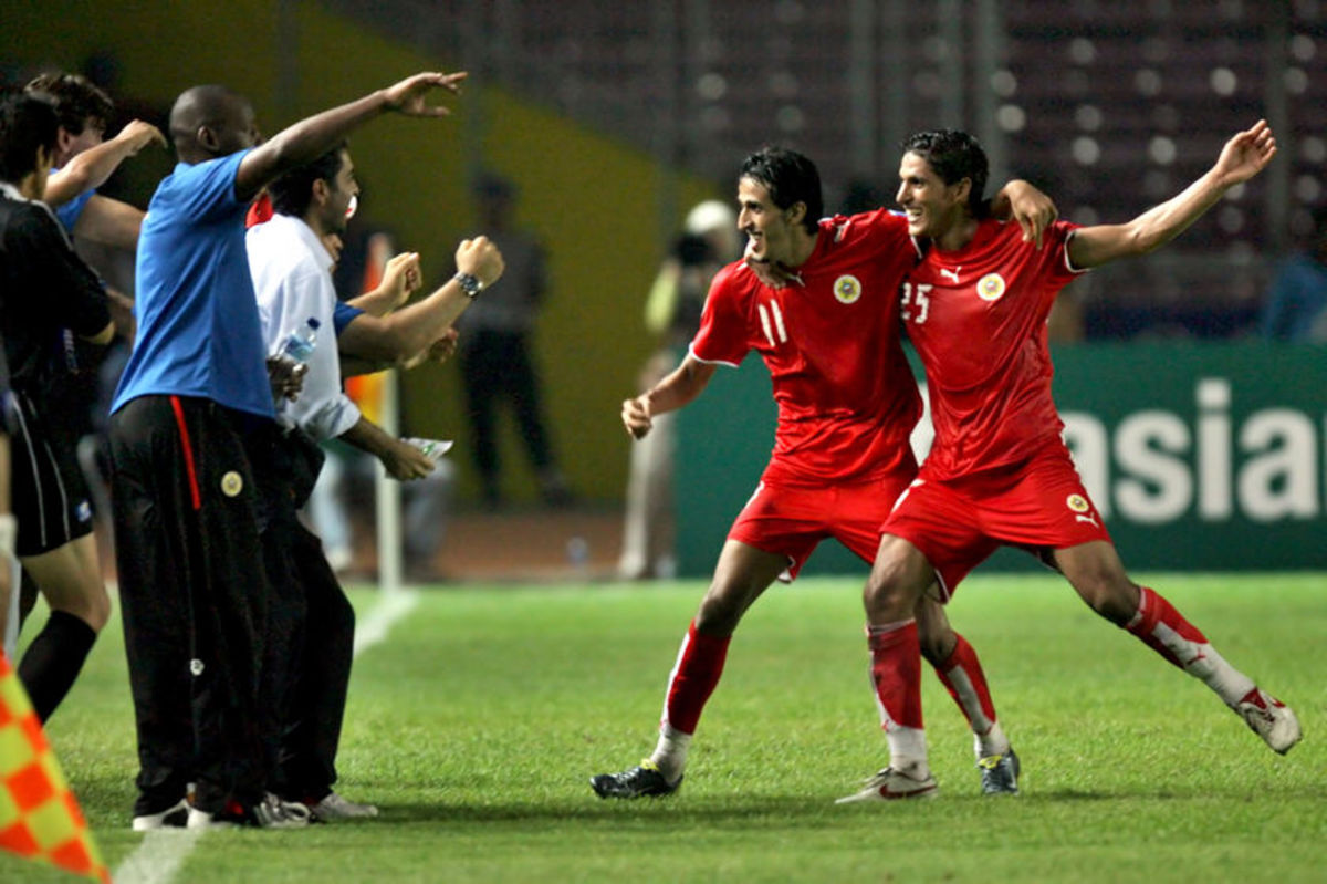 Ismail Abdul-Latif (11) and Faouzi Mubarak Aaish (25) celebrate with personnel after Abdul-Latif scored the winning goal to give Bahrain a shocking 2-1 victory over South Korea