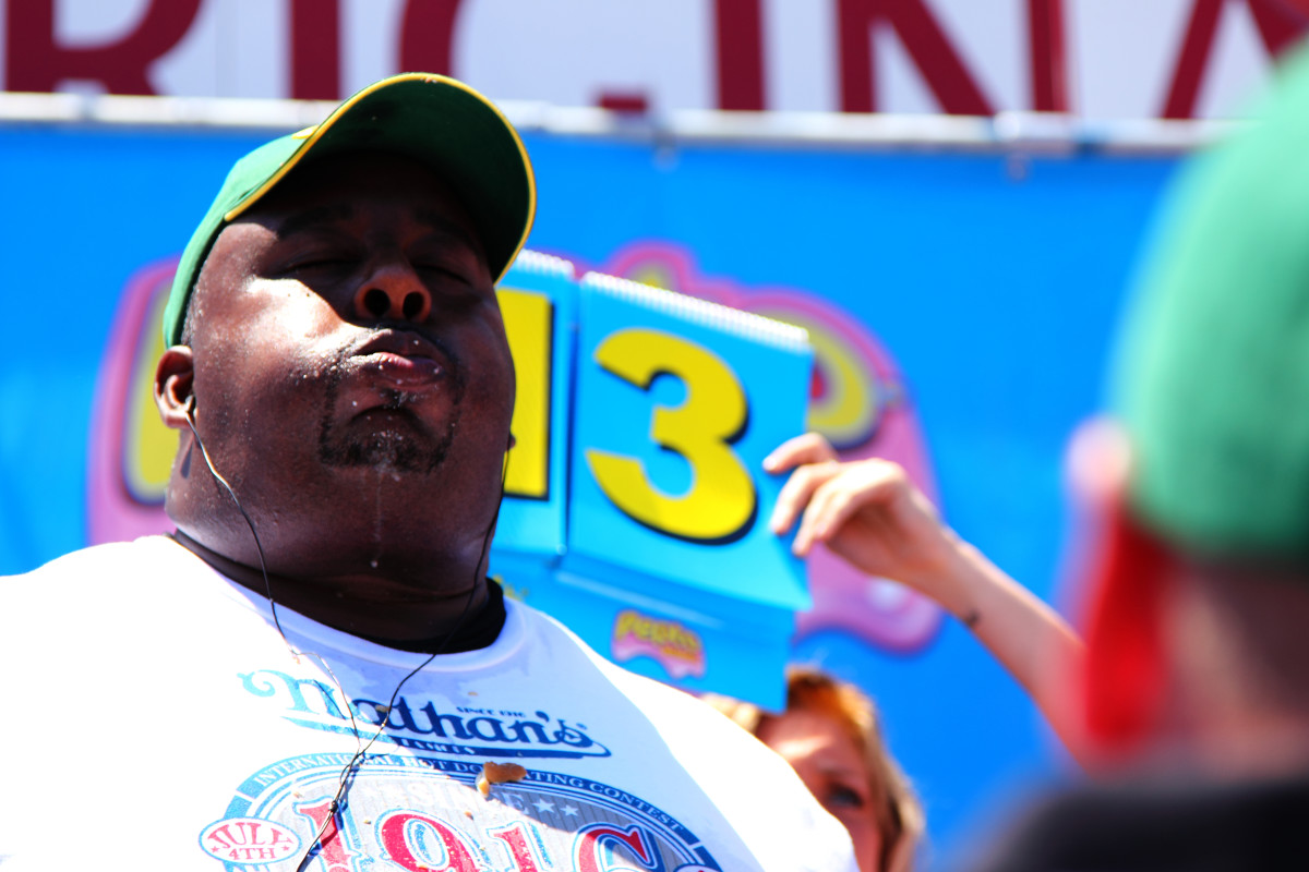 Eric Booker packs in his 14th hot dog in the 2010 Nathan's competitive hot dog eating contest.  Despite what you might think, not all competitive eaters are large.