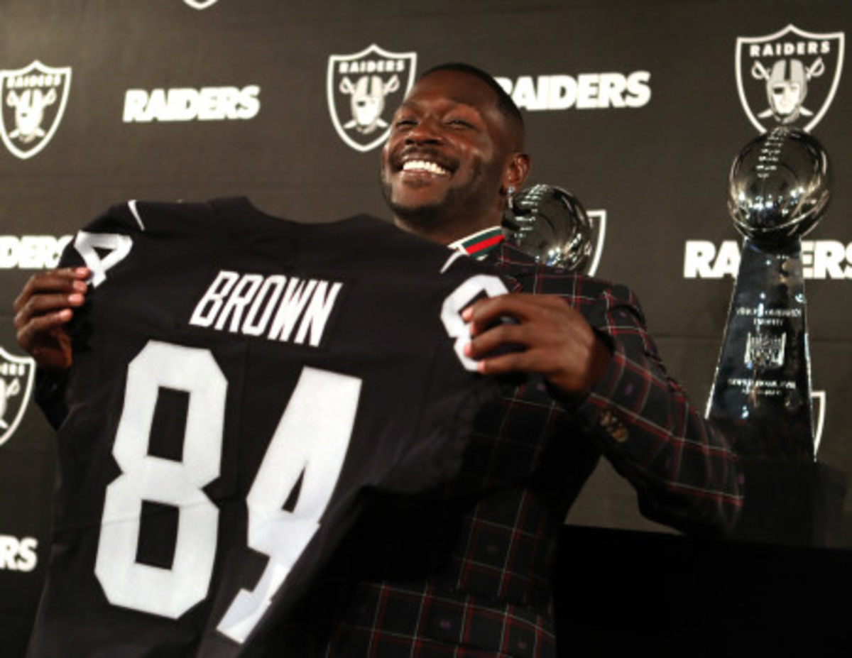 Brown holding a Raiders jersey.