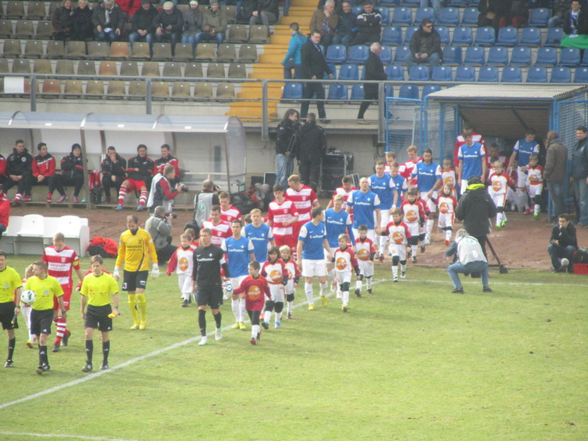 Players walk onto the field at Stadion am Böllenfalltor on Mar. 3, 2013 between SV Darmstadt 98 and Hallescher FC. SV Darmstadt 98 lost this match 2-1 as the club finished 14th in the 2012-13 3. Liga.