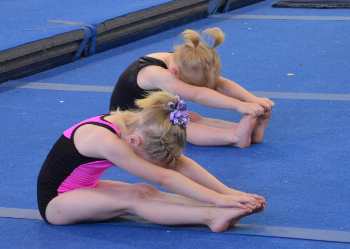 Young gymnasts learning to stretch.