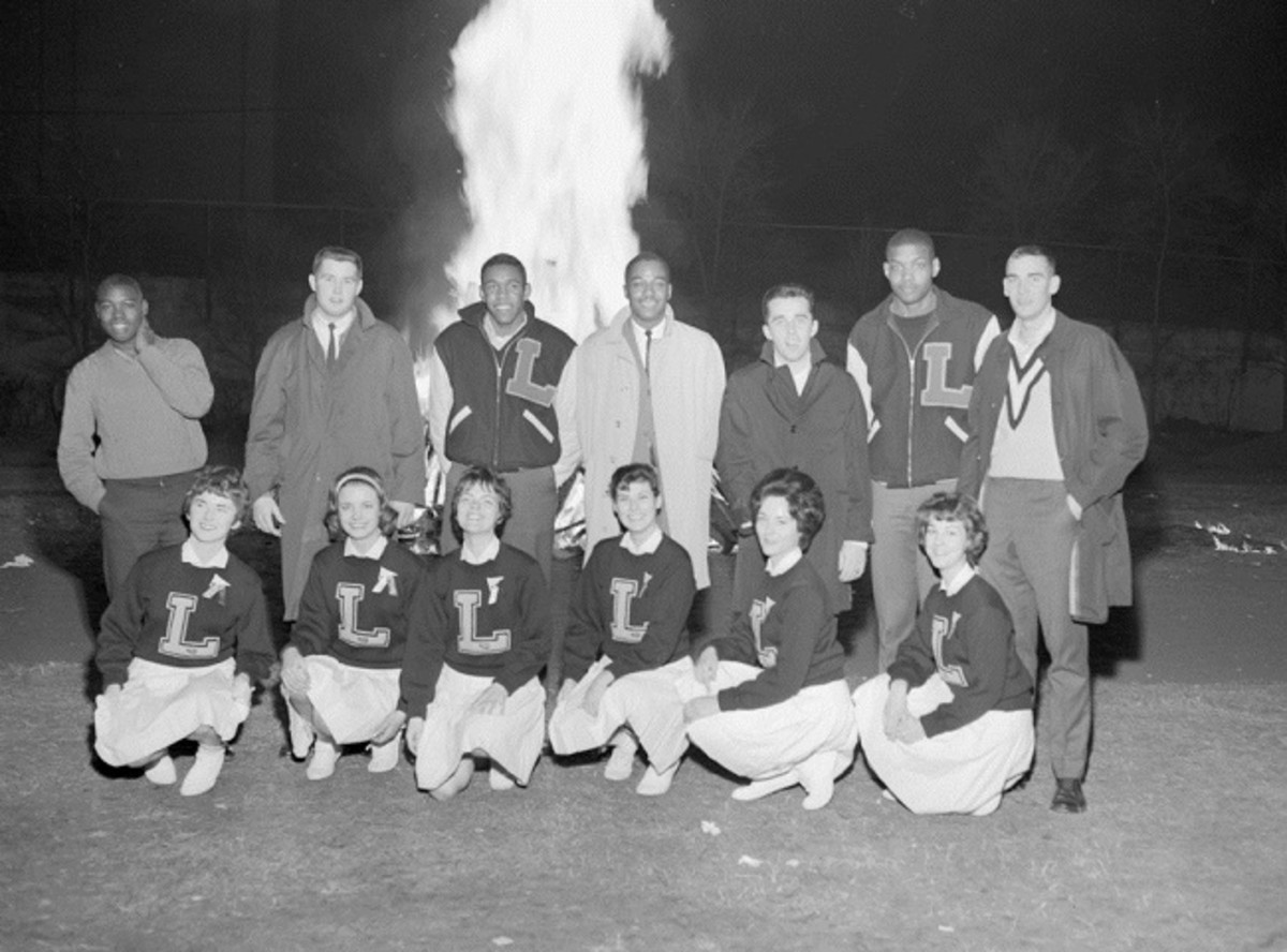 Players and  cheerleaders celebrate the beginning of basketball season in front of a bonfire at Pow Wow Weekend, November 30, 1962.