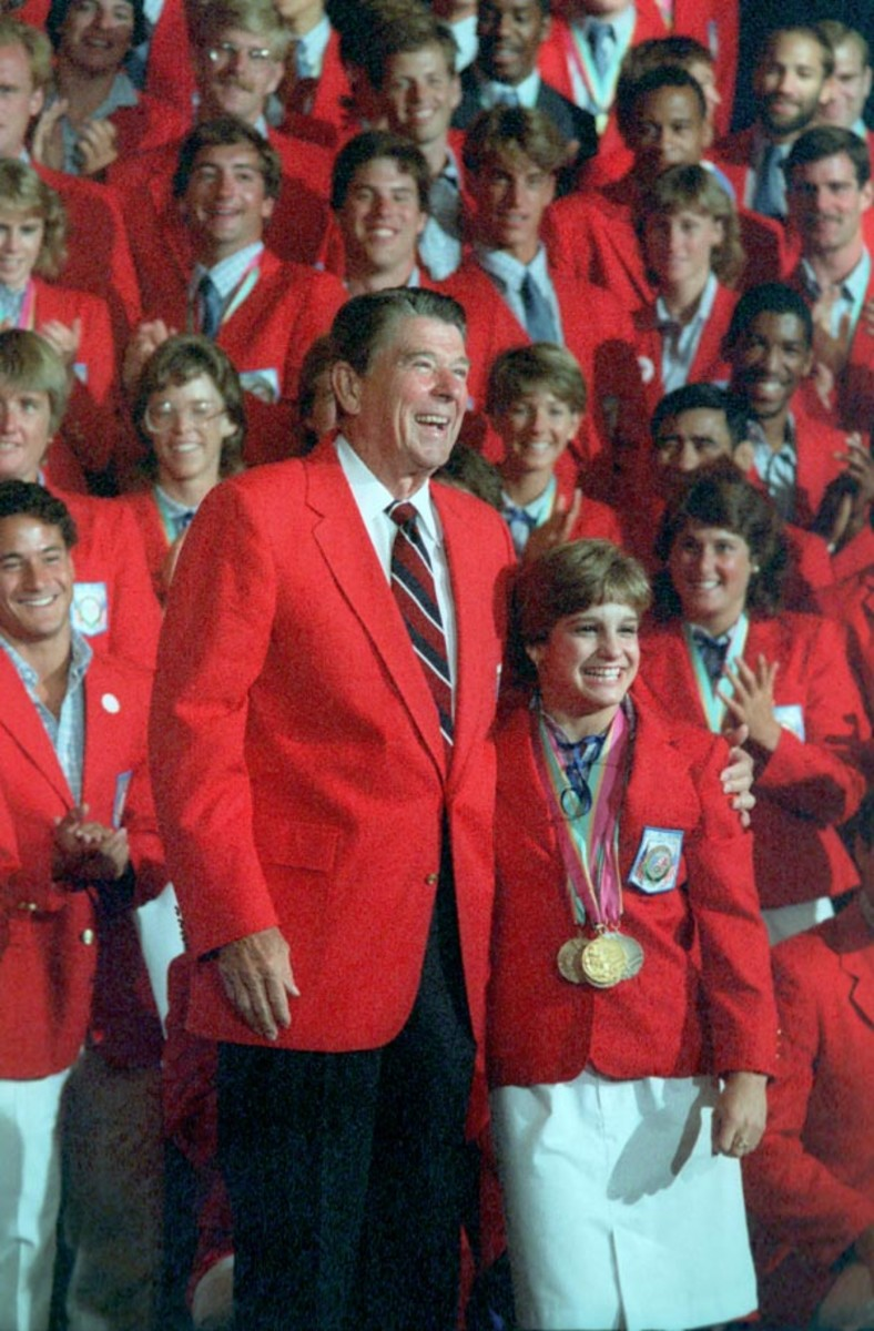 """Perky Mary Lou Retton was one of America's darlings for the gymnastics team.  Posing here with President Ronald Reagan who towers over the 5'2"""" star as the US Olympic Team looks on."""