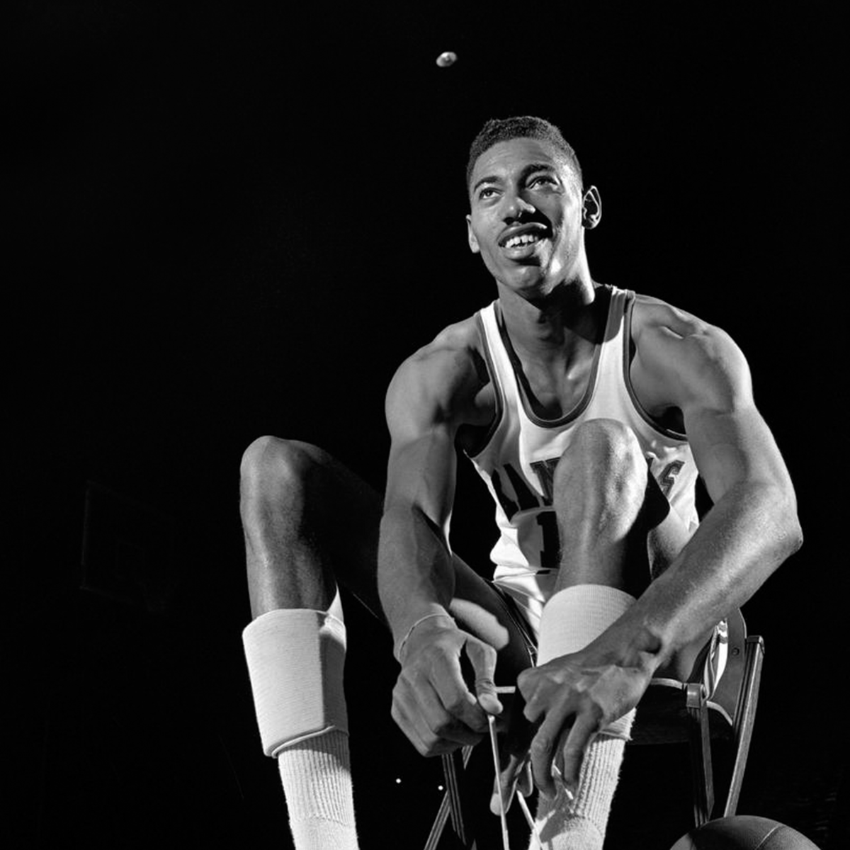 Wilt Chamberlain fixing his shoelace.