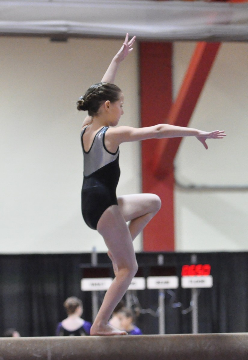 A young girl practicing on a beam post