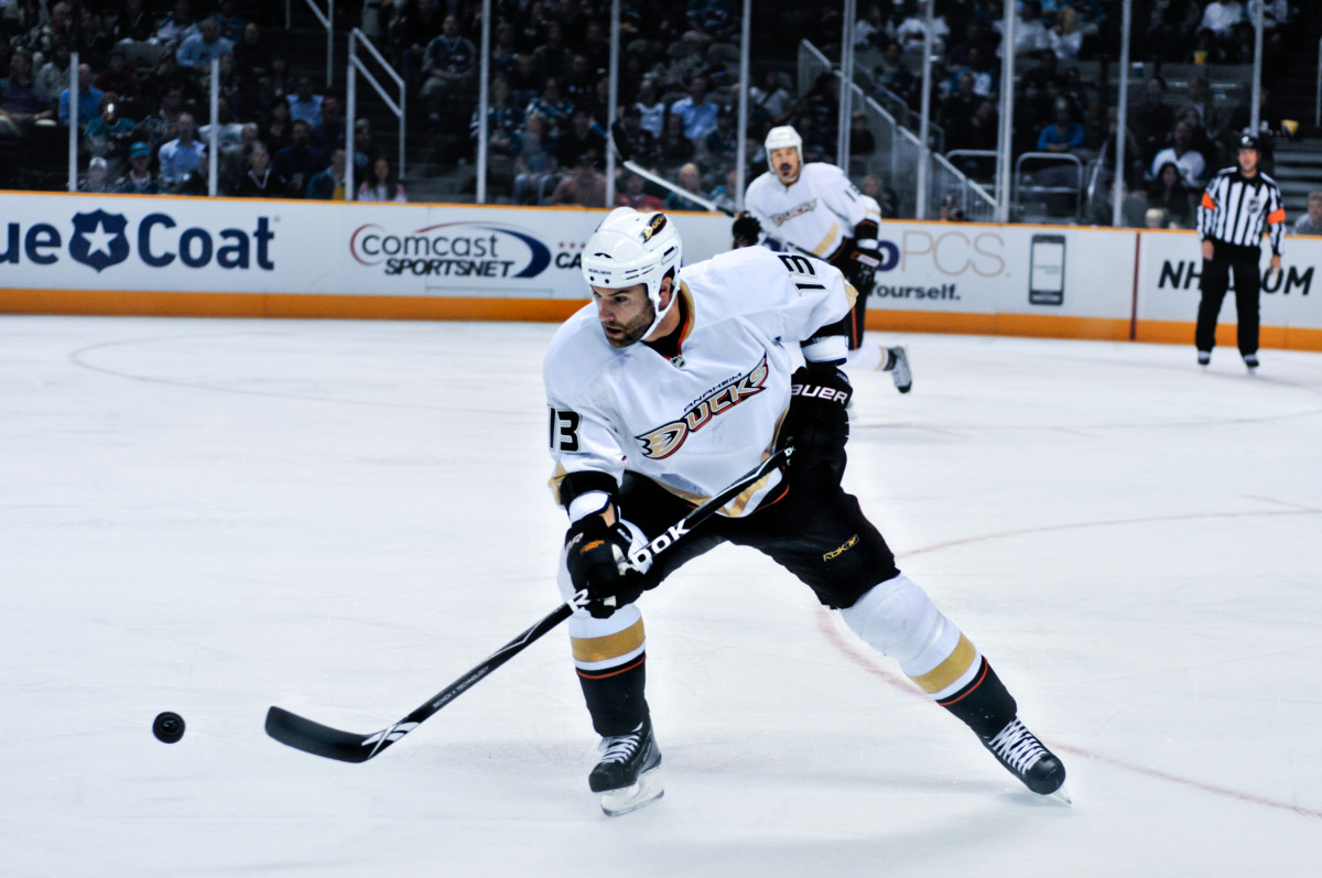 A hockey player is skating on ice while holding a hockey stick. He is going for the puck.