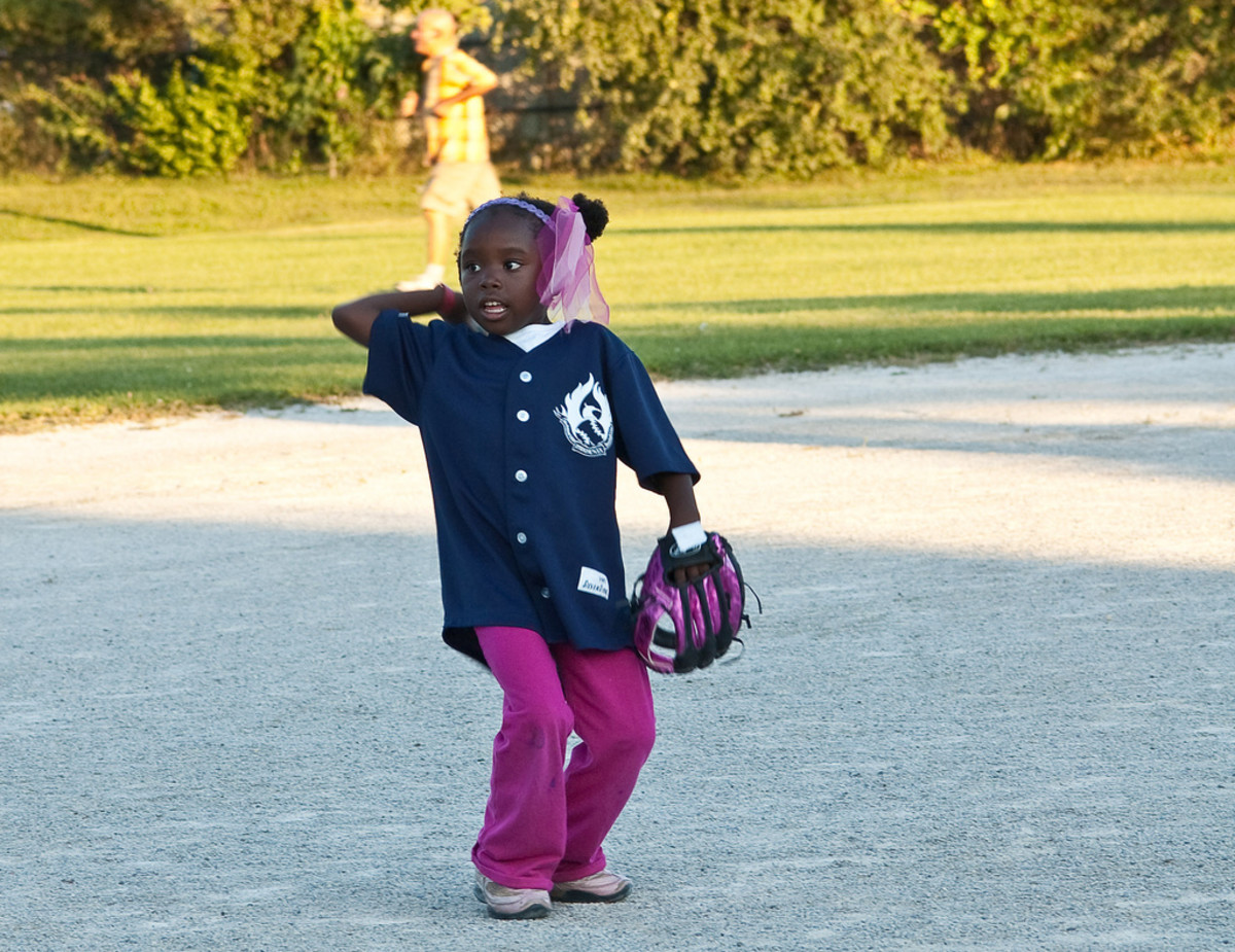 A little girl throwing a ball.