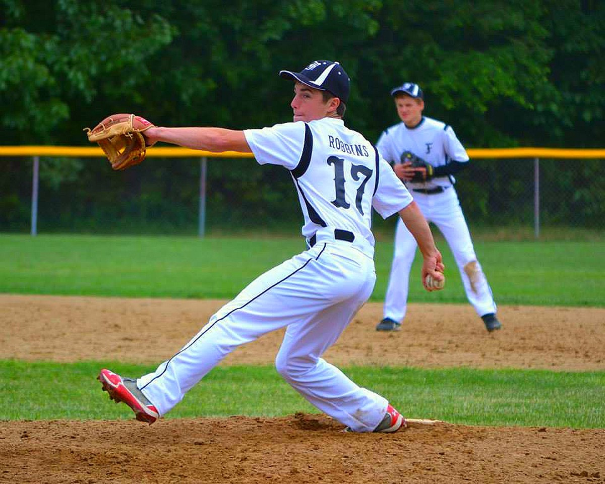 As the leg kicks forward, notice how the arms are spread like wings. This extension is important; throwing the glove out toward the plate and reaching back toward 2nd base with the ball.