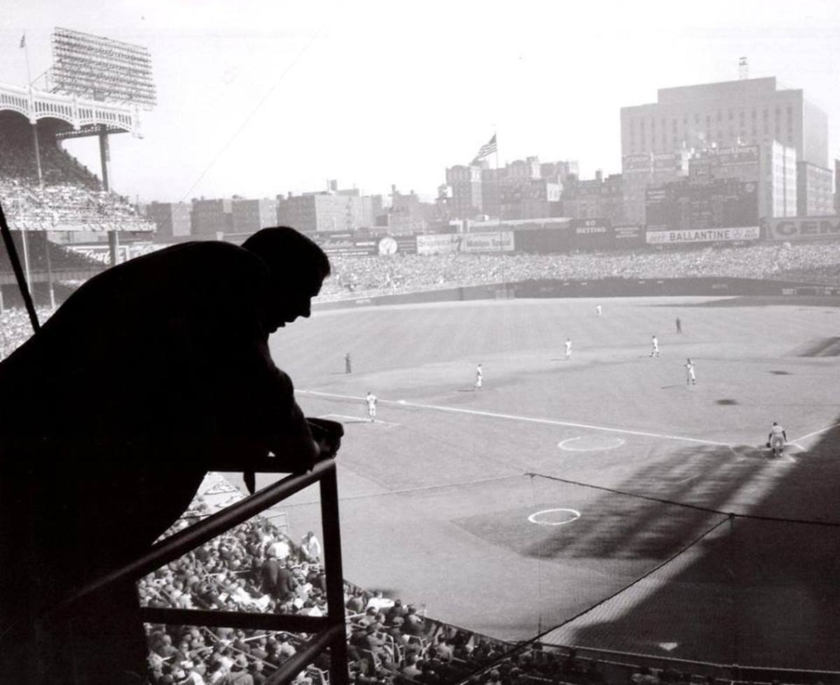 A retired Joe DiMaggio looks out from the press box at Yankee Stadium during Game 1 of the 1957 World Series. This is a brilliant photo that speaks to the viewer. Recently divorced from Marilyn Monroe, he was at a crossroads in his life.