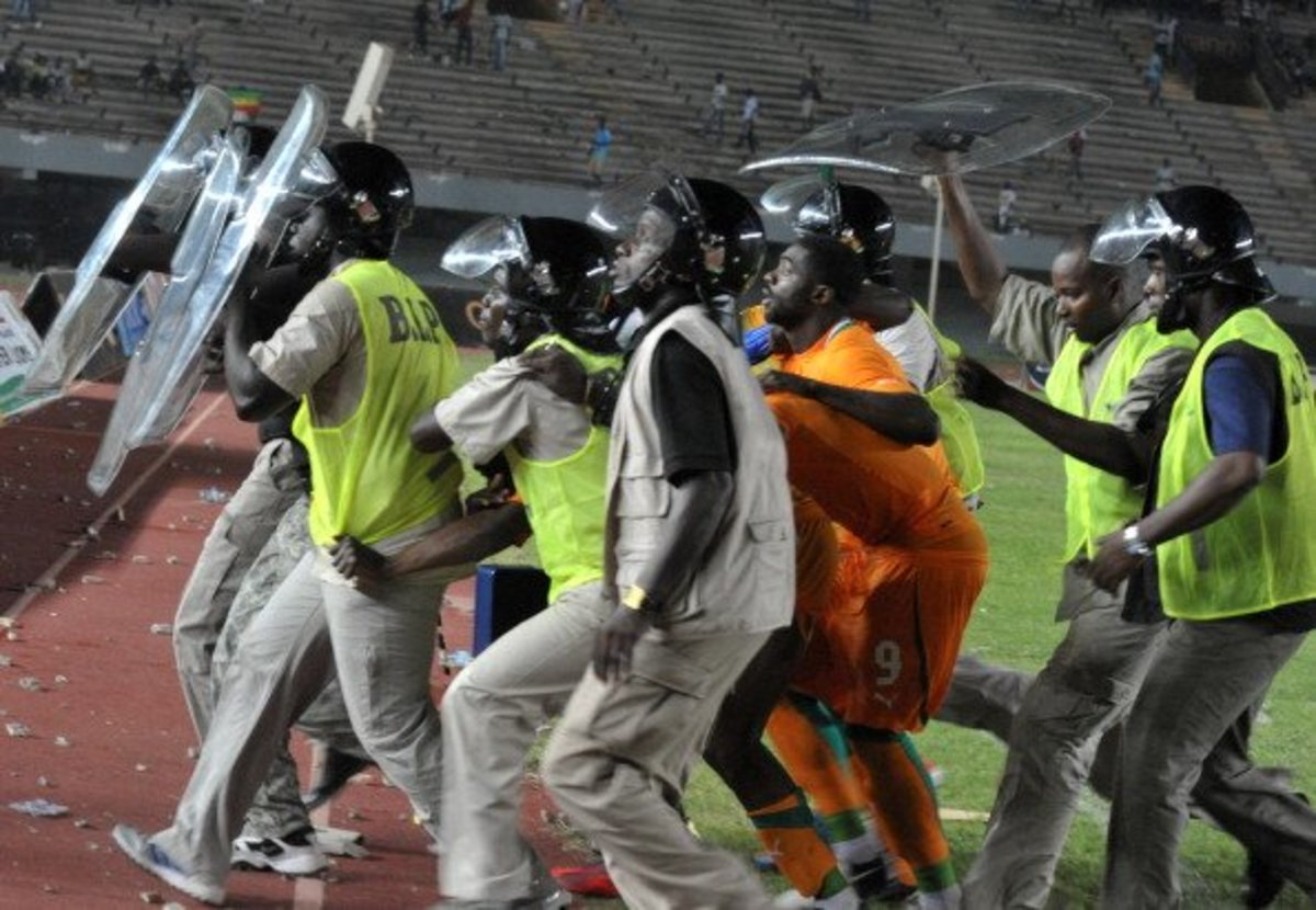 Police escort players from Ivory Coast as fans rioted during Senegal's second leg against Ivory Coast in a 2013 AFCON qualifier in Dakar, Senegal.