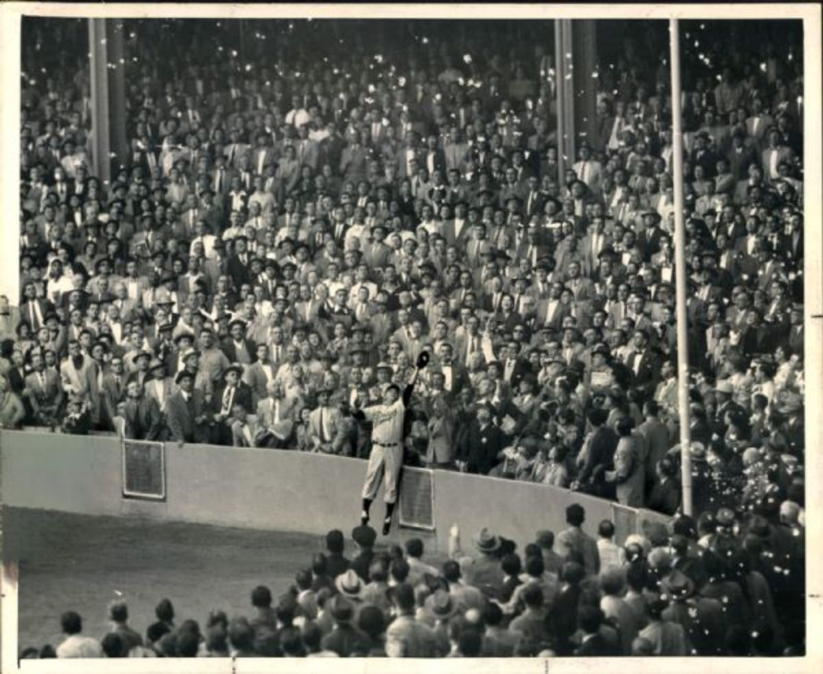 Furillo at Yankee Stadium, 1955 World Series. Can't believe almost everyone in the crowd is wearing a suit.  The wall was much lower then and it was only 299 feet down the line.