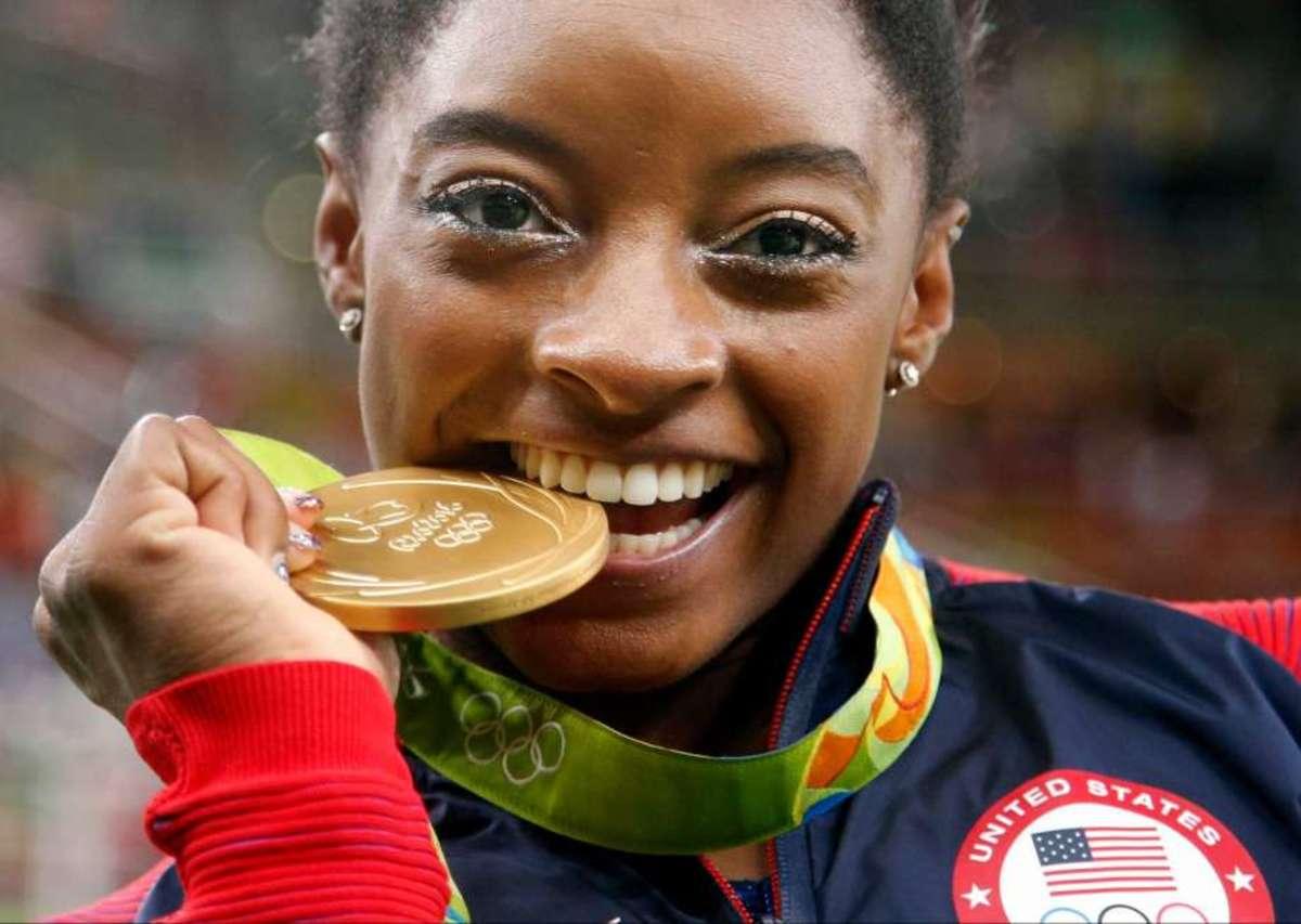 Simone Biles biting her gold medal.