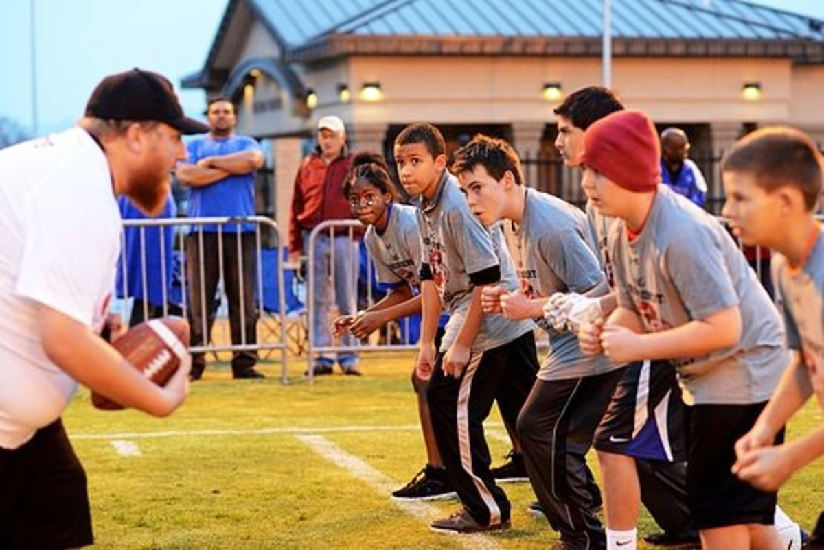 Youth football players at Luke Air Force Base conduct physical fitness drills.