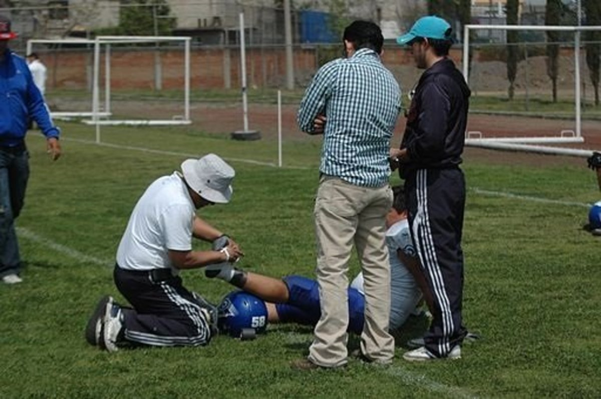 Youth football player having his ankle taped after an in-game injury.
