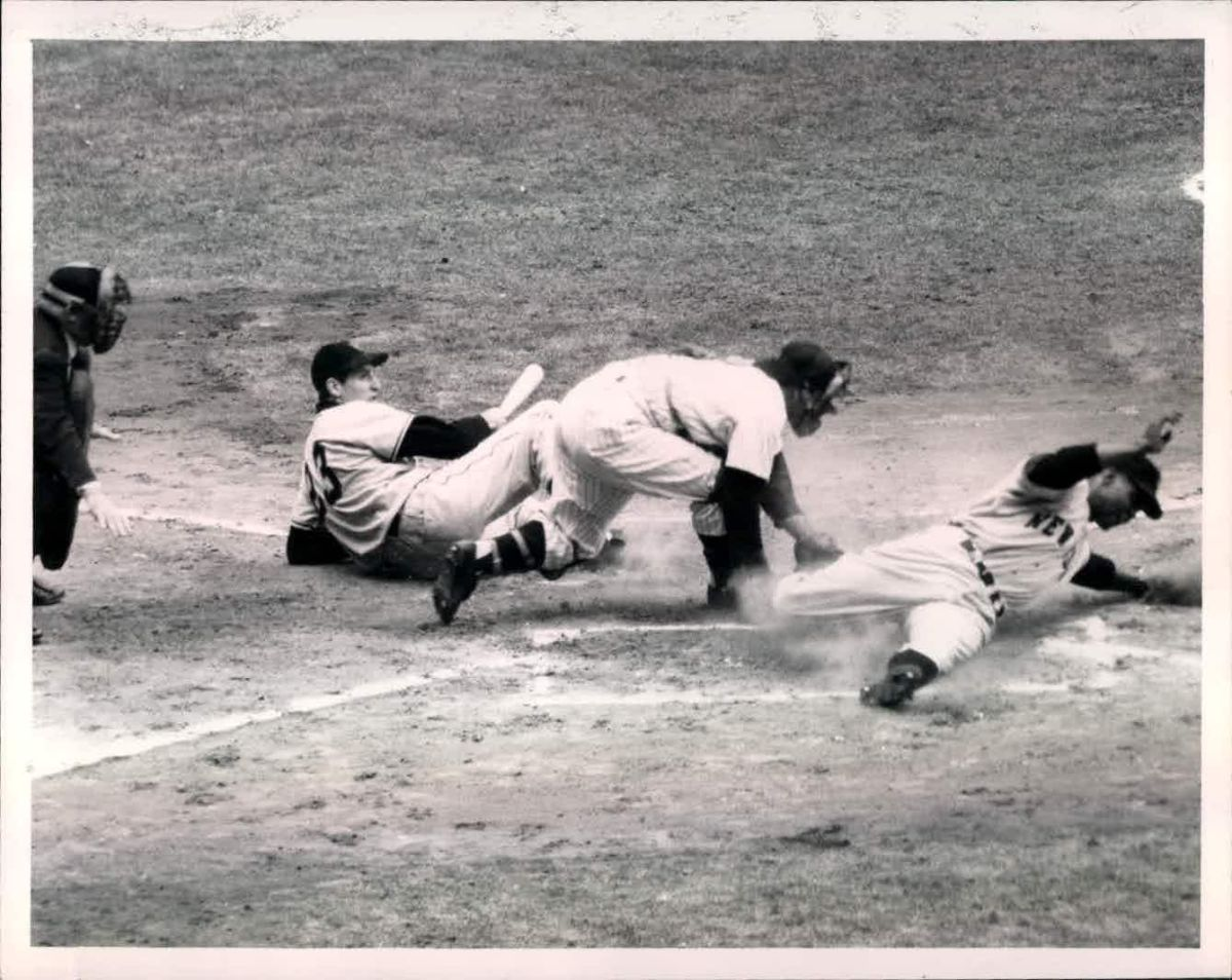 Monte Irvin steals home during Game 1 while Bobby Thomson leaps out of the way.