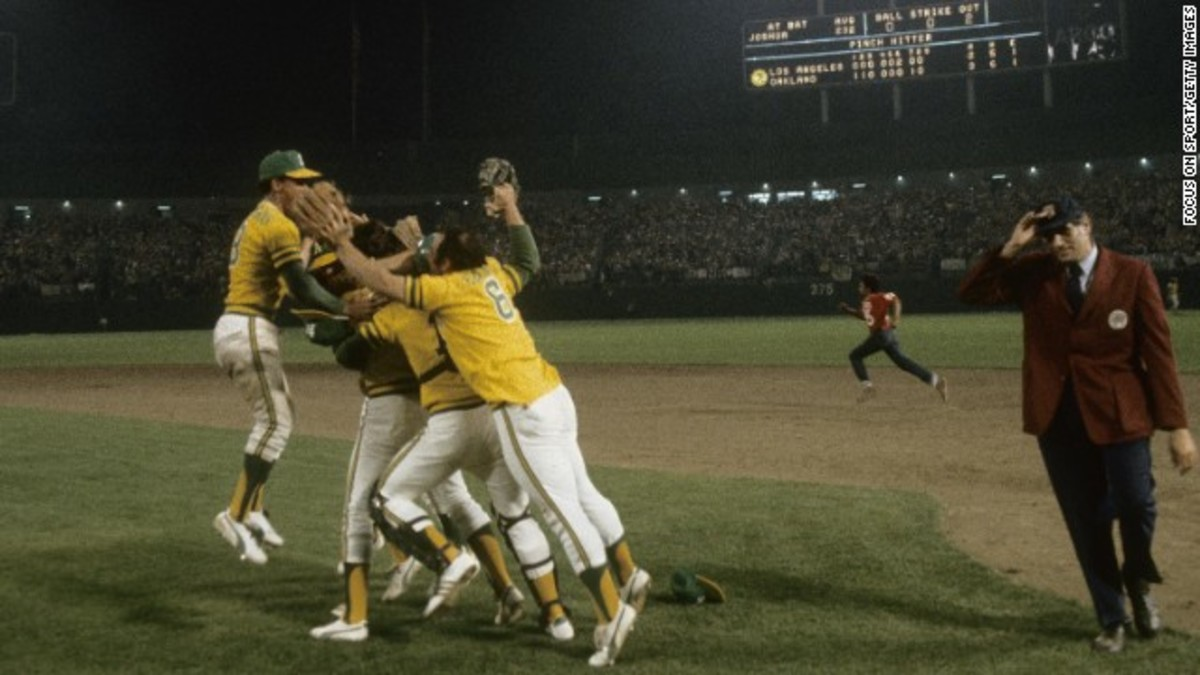 A's celebrate their third straight World Series Championship as umpire Ron Luciano tries to get off the field.