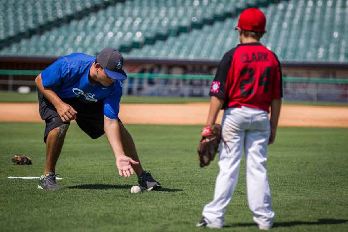 a little league coach working with a player