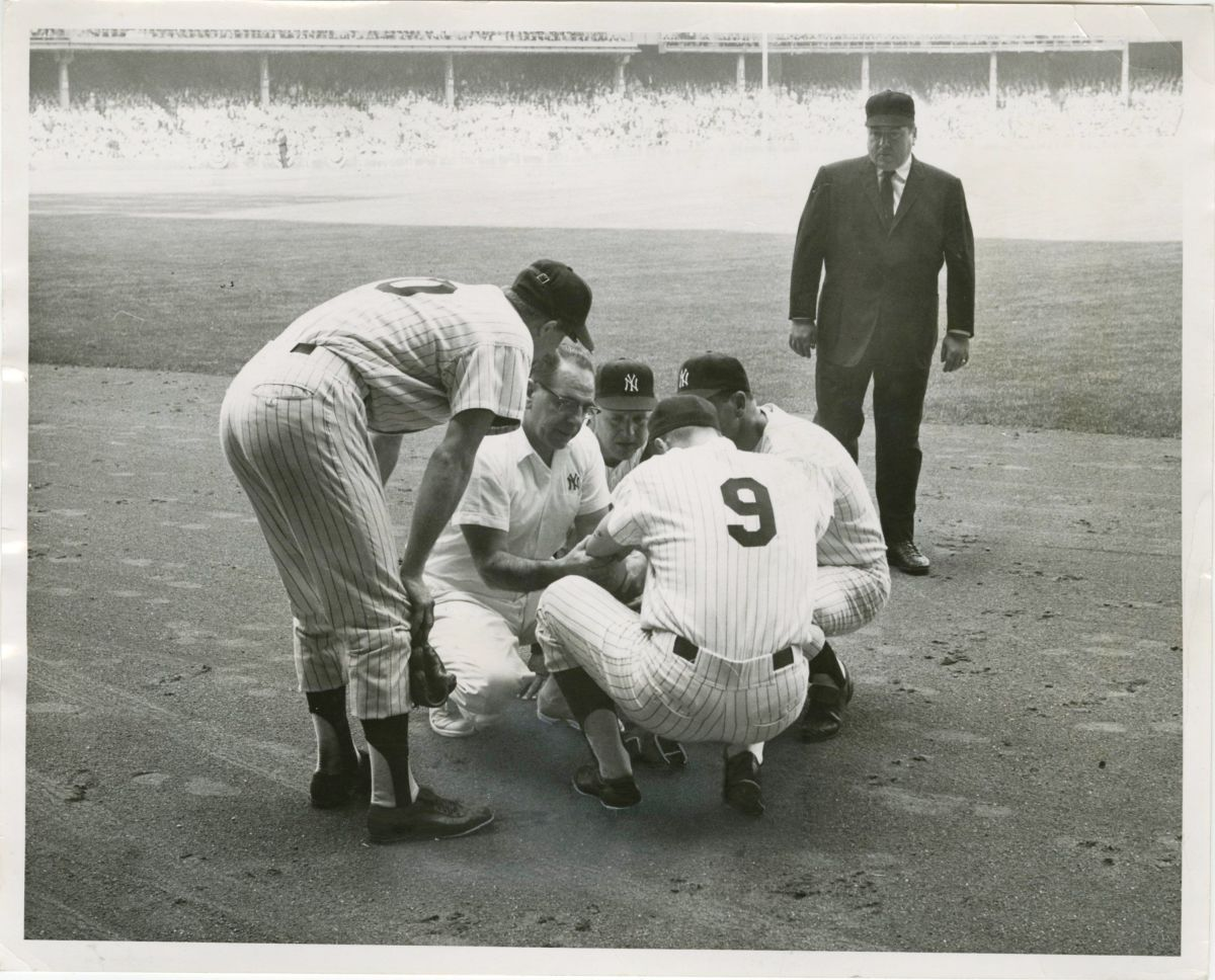 3rd inning, Game 2: Roger Maris is being checked out by the trainer and Houk. Joe Pepitone and umpire John Rice look on.