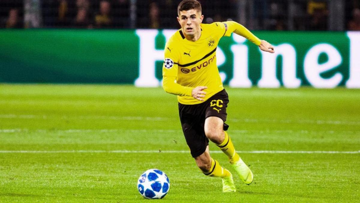 Christian Pulisic dribbling a soccer ball downfield playing for Dortmund.
