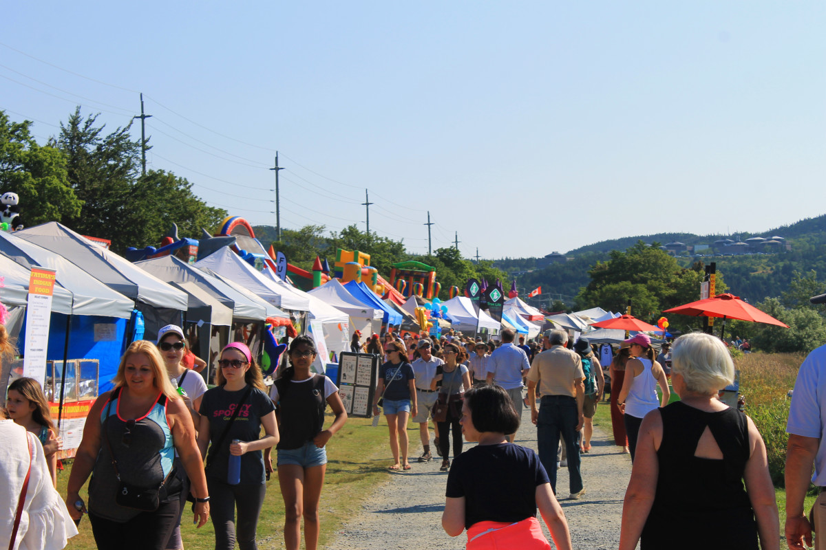 Crowds stroll past games, and food vendors, pond side, 2018 Royal St. John's Regatta.