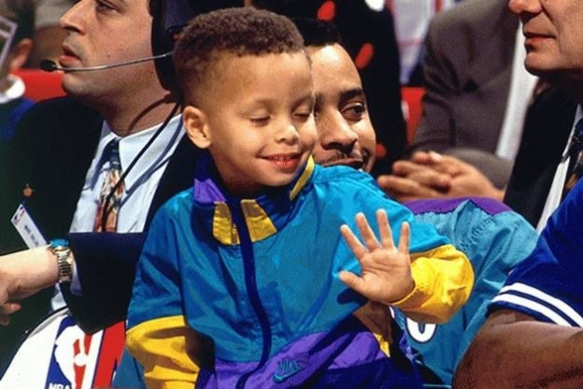Steph sits with his father, Dell, at a basketball game.