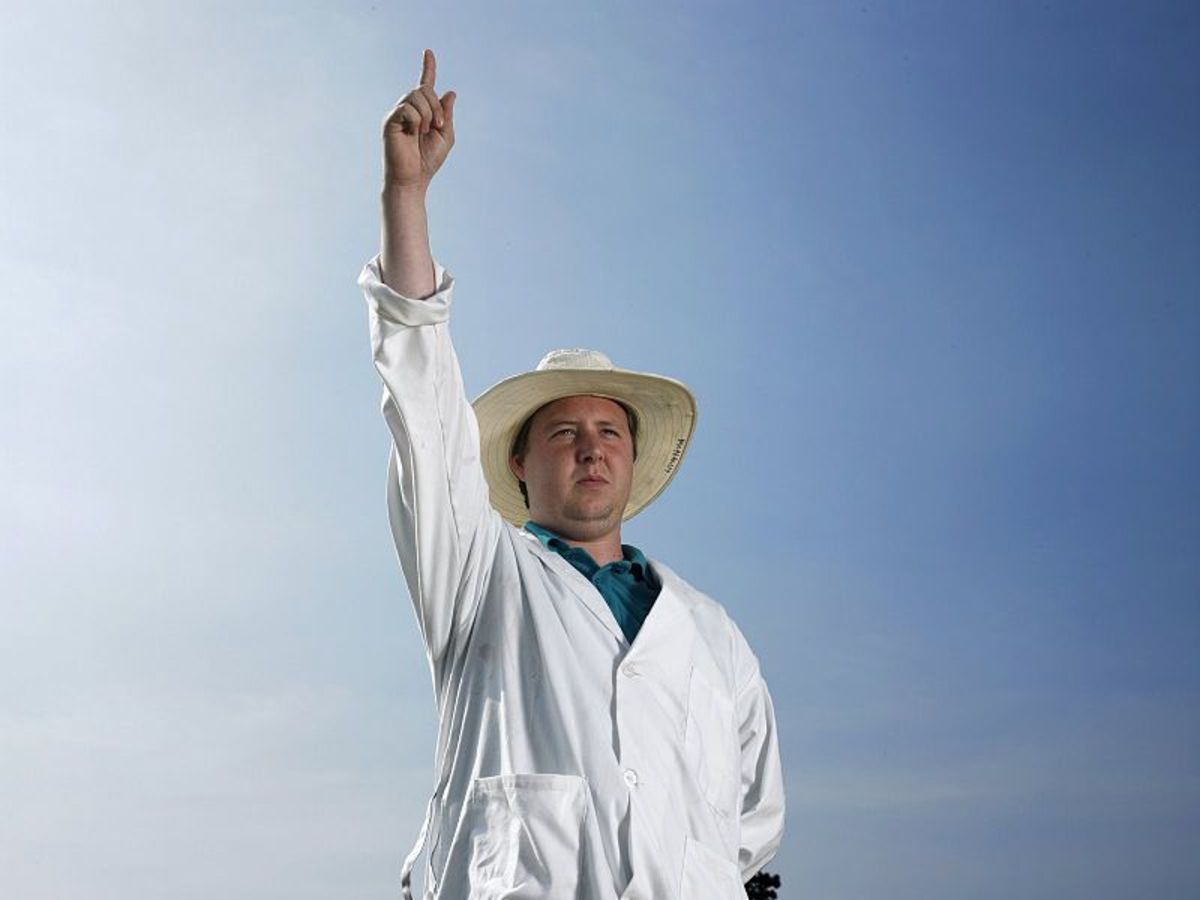 A Cricket umpire giving the typical signal telling a batsman that they are out.