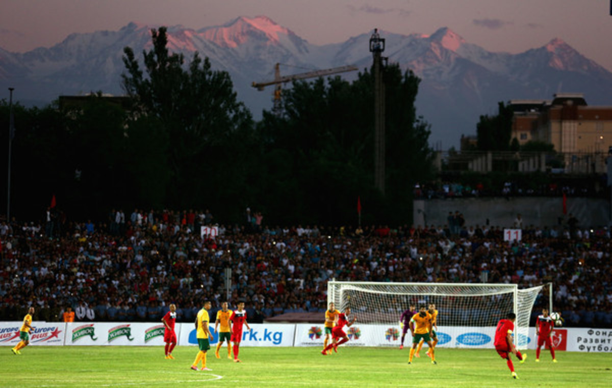 Azamat Baimatov (#7, red) attempts a shot during a 2018 FIFA World Cup qualifier between Kyrgyzstan and Australia on June 15, 2015 at Dolen Omurzakov Stadium in Bishkek, Kyrgyzstan