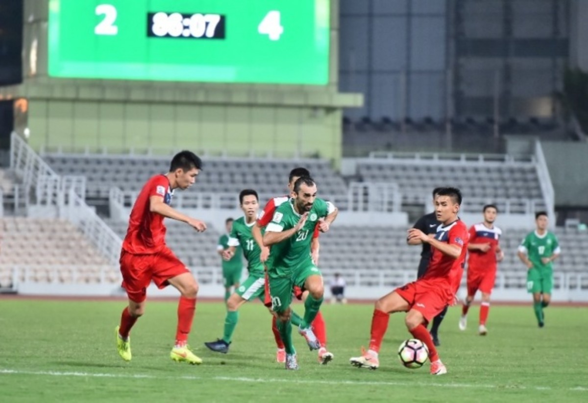 Kyrgyzstan players (red jersey) battle for possession during the second half of a 2019 Asian Cup qualifier at Estádio Campo Desportivo in Macau.