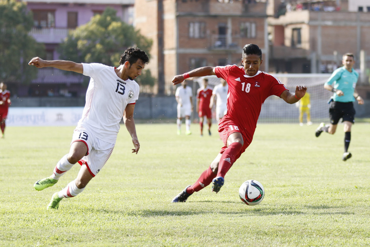 A Yemeni player (white) and a Nepali player (red) battle for possession of the ball during a 2019 Asian Cup third round qualifier on June 2017 at Halchowk Stadium in Kathmandu, Nepal.