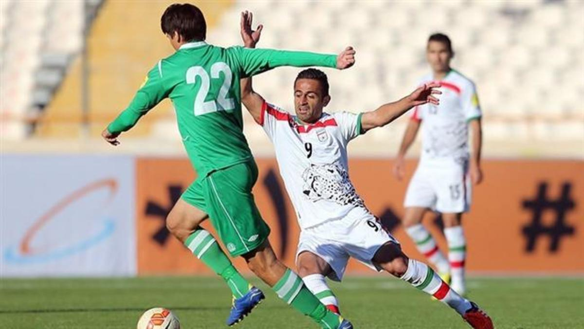 Seldar Geldiyev of Turkmenistan (22, green) attempts to evade a tackle from Omid Ebrahimi (9, white) during a 2018 FIFA World Cup qualifier on November 12, 2015 in Tehran, Iran. The match, played at Azadi Stadium, ended 3-1 to Iran.