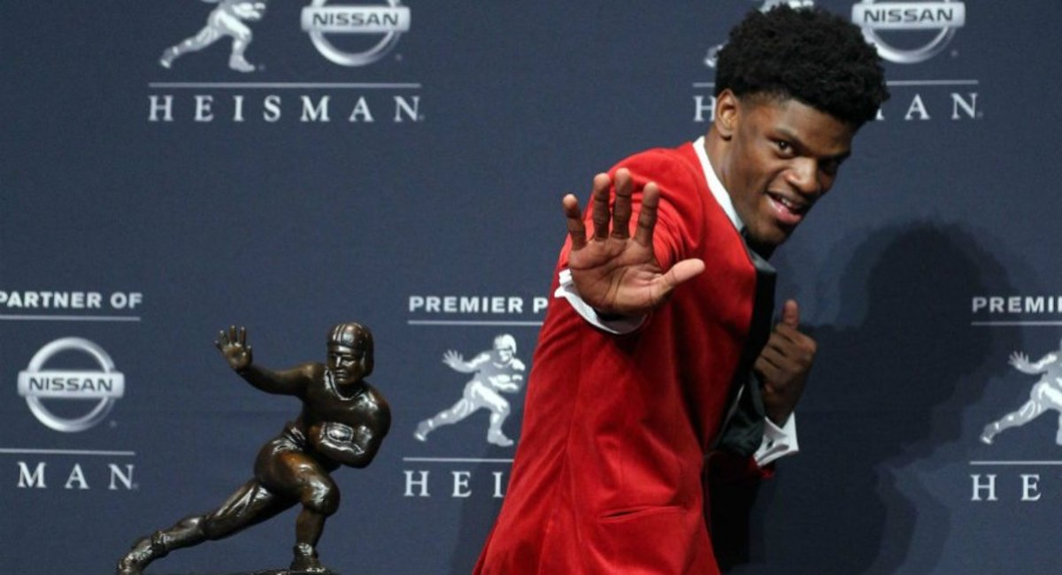 Lamar Jackson posing with the Heismas Trophy in 2016.