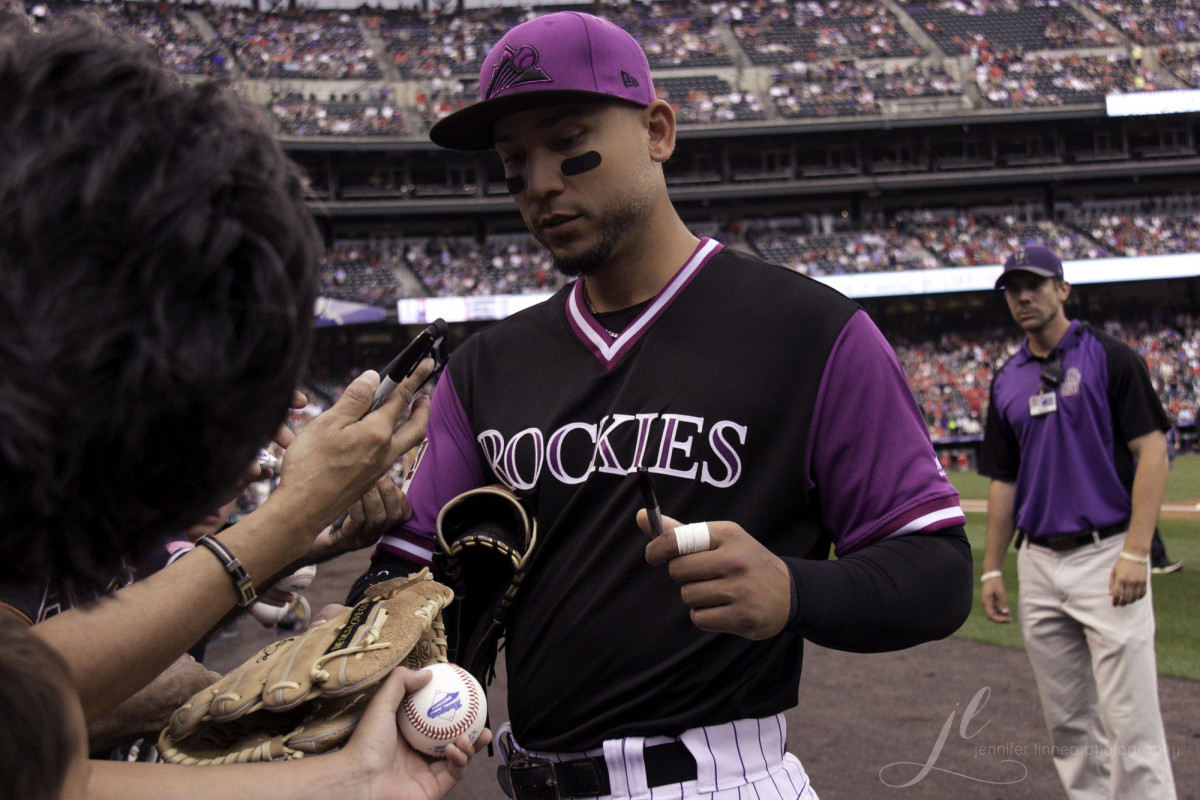 Former Colorado Rockies outfielder Carlos Gonzalez signs an autograph for a fan during the 2018 season.