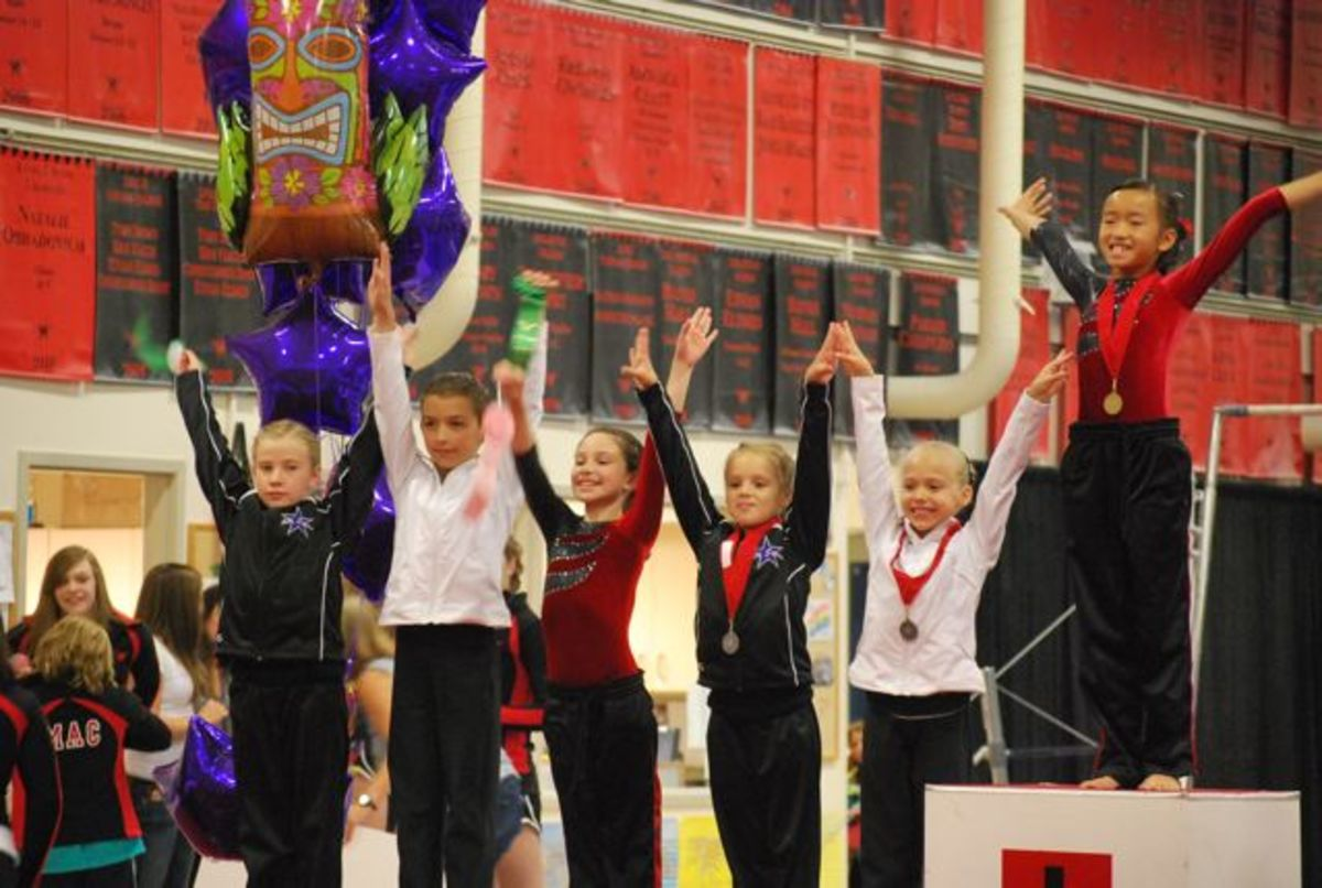 Gymnasts salute on the awards podium