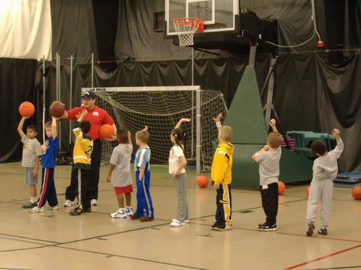 Coach teaches shooting position.