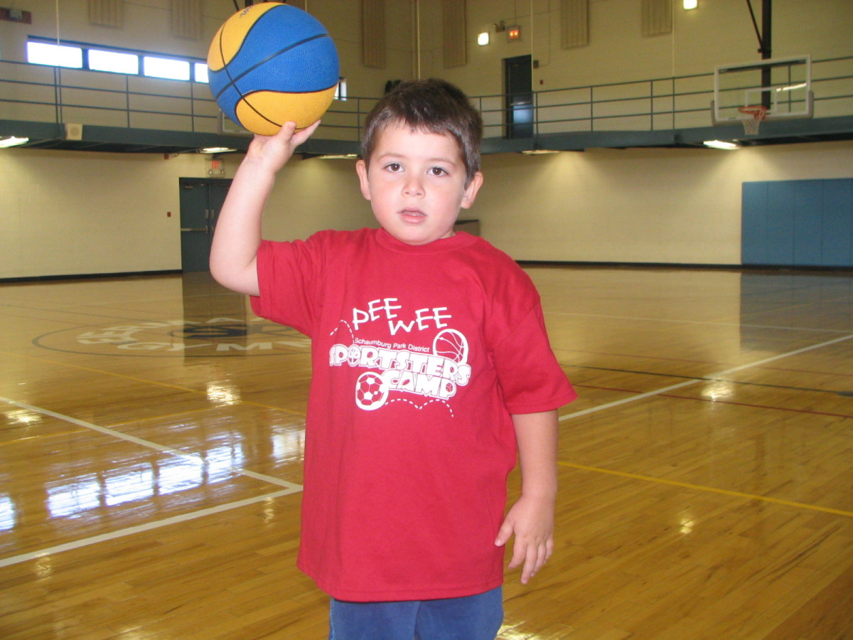 Boy balancing a basketball on one hand