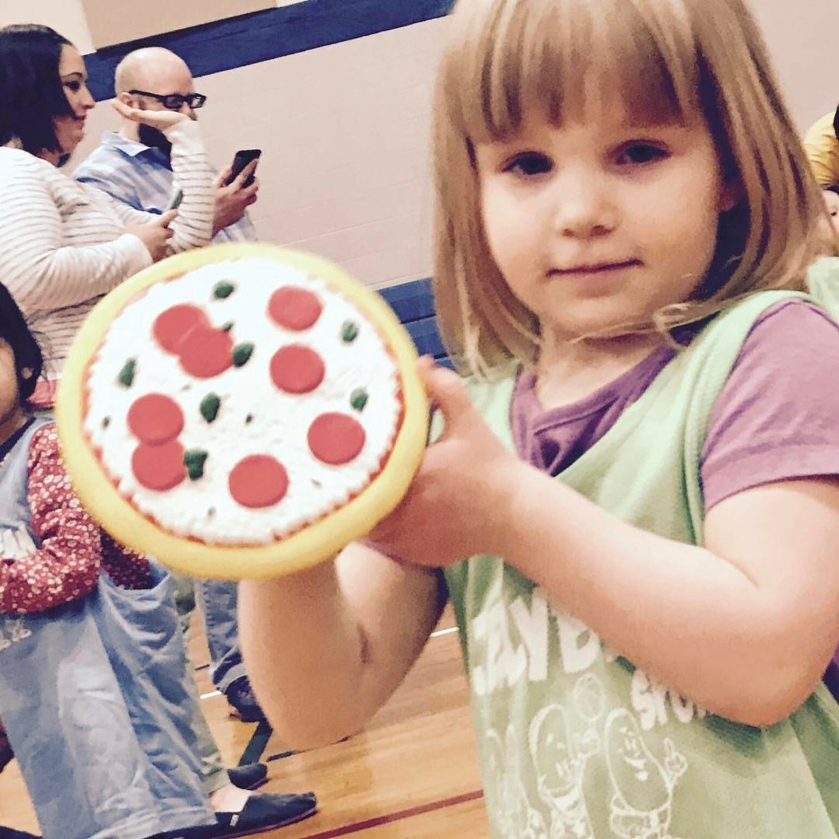 Basketball prep: A girl holds a foam pizza.