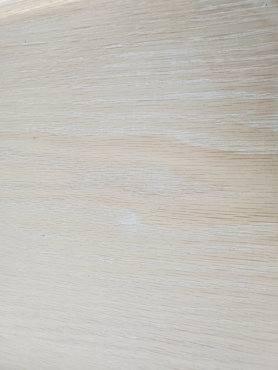 A close-up of oak I skim-coated with grain filler.