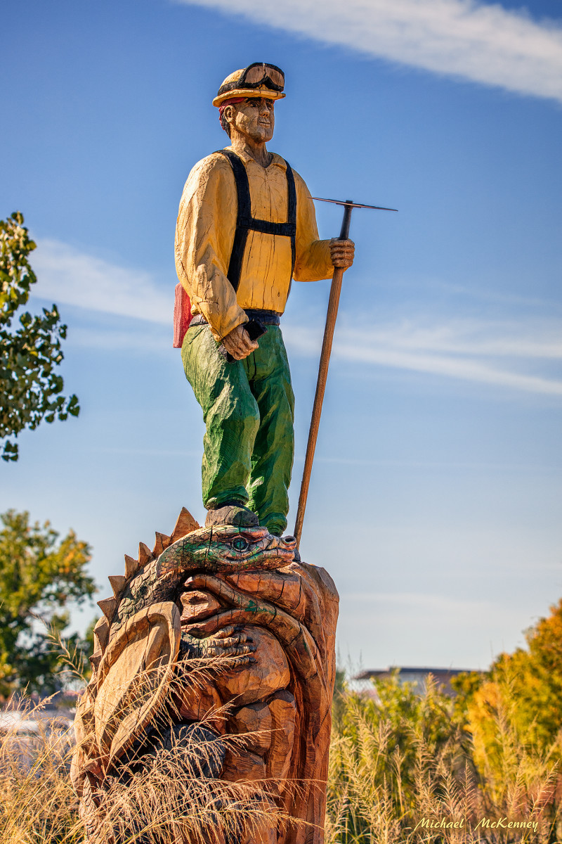 This chainsaw carving by Mark Chavez shows a firefighter standing upon the head of a dragon.  A dragon is a firefighter's slang word for a particularly bad fire.