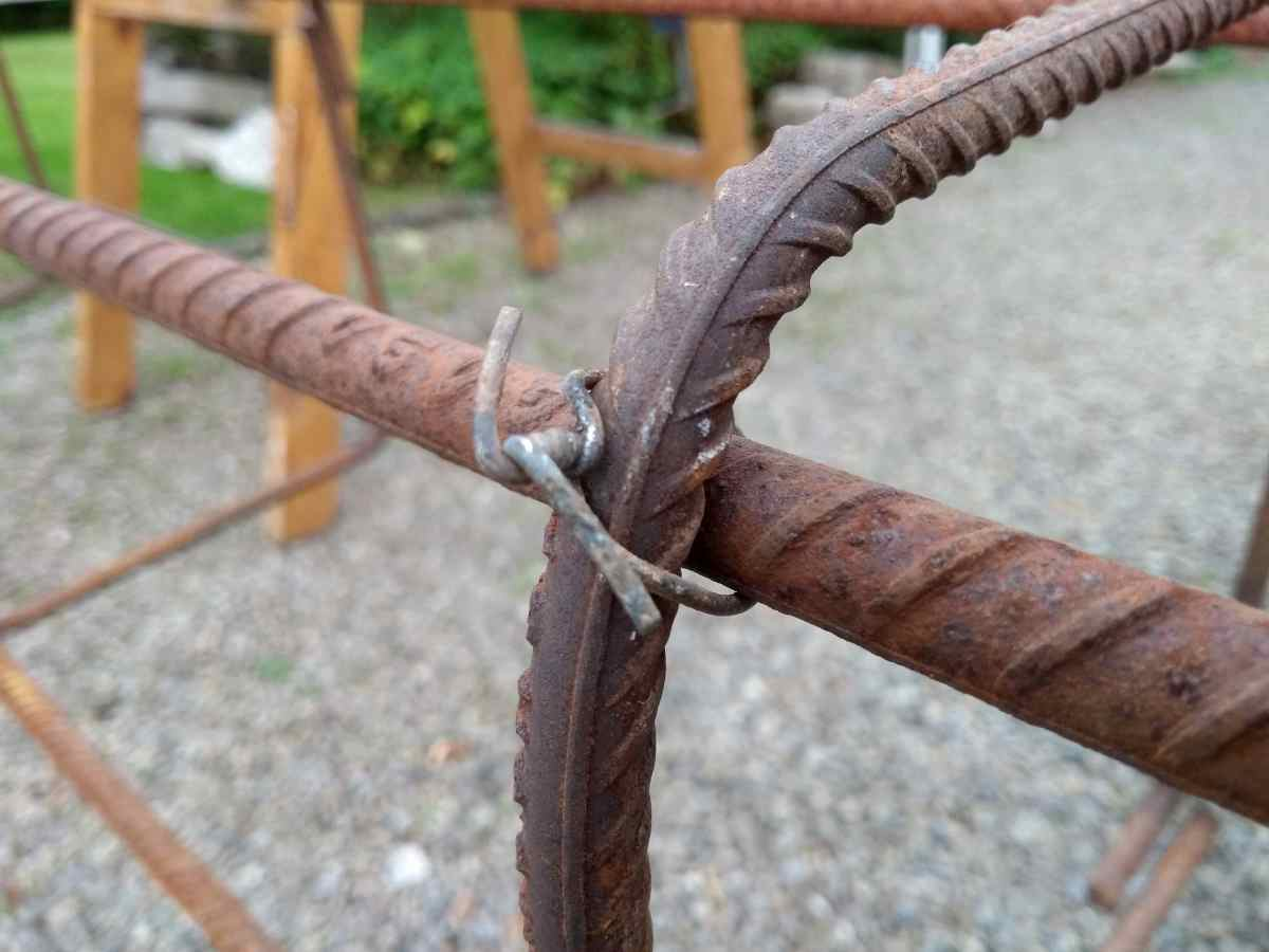 Sections of rebar are held together by steel wire, twisted together with a pliers.