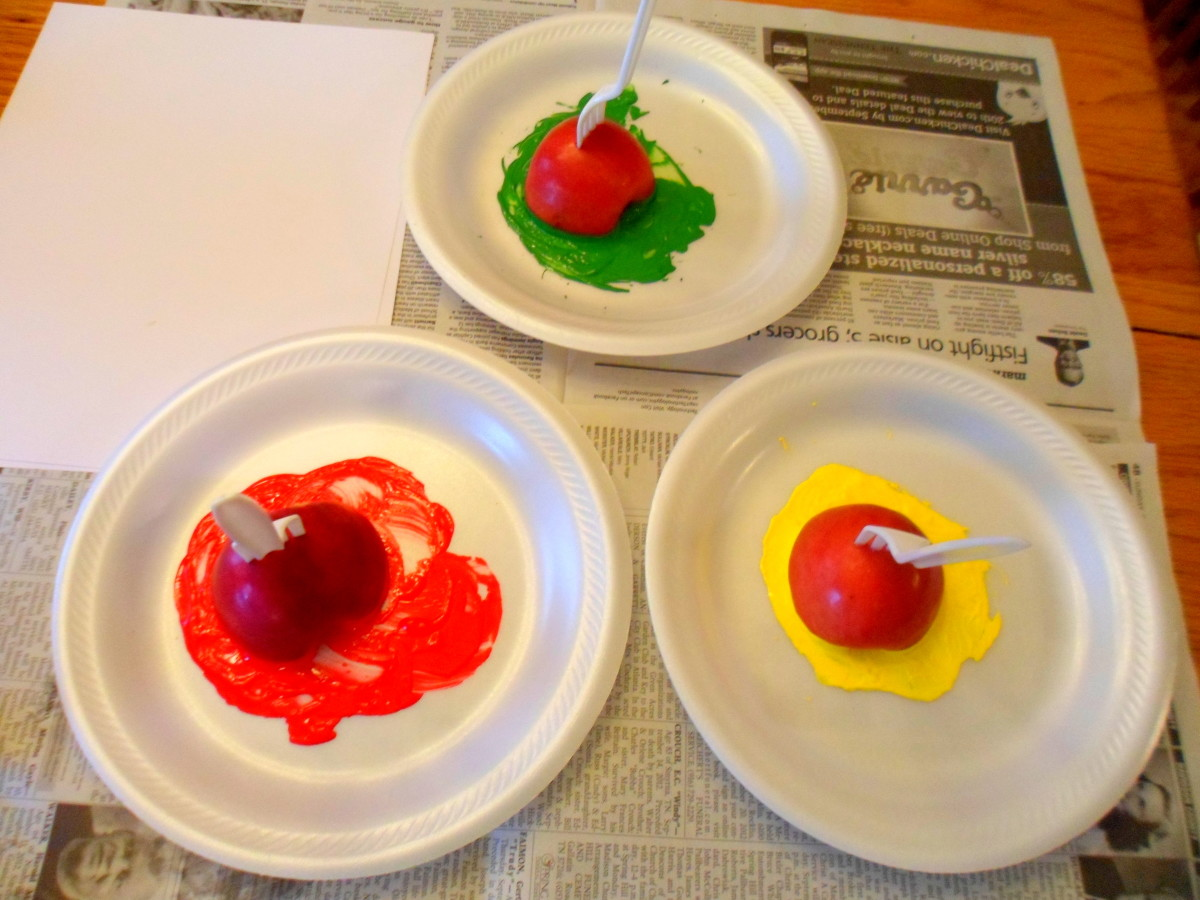 Cut apples in half and squirt out green, red, and yellow paint on paper plates.