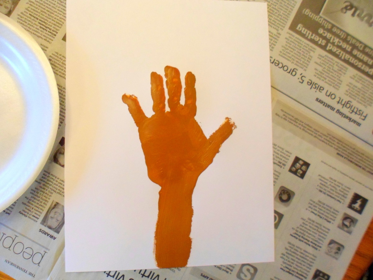 Paint the child's hand and arm brown and press on paper to make tree trunk.
