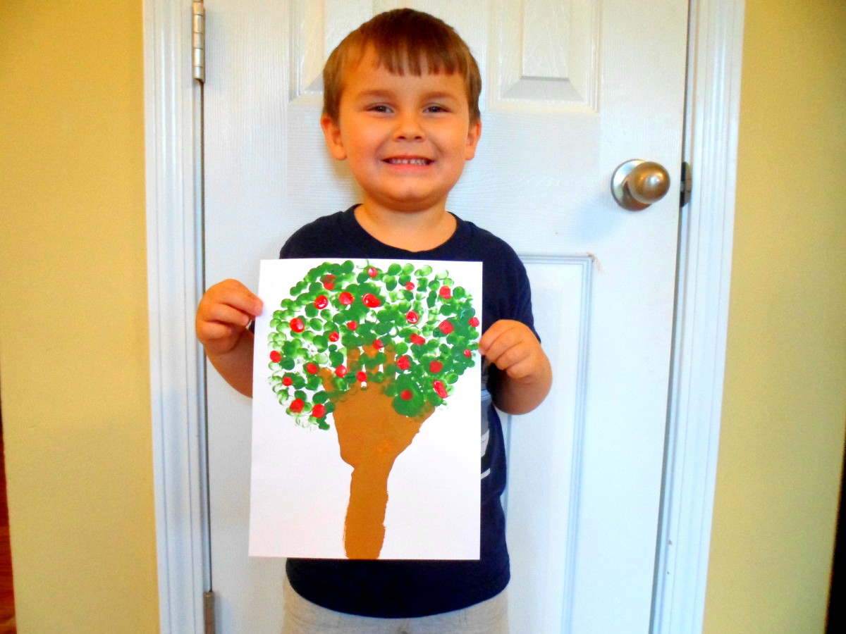 My son proudly displaying his apple tree.