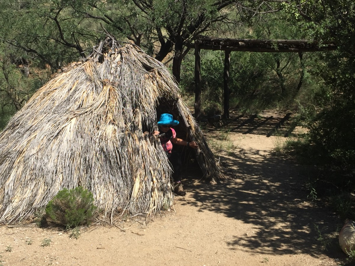 My wife emerging from replica of Apache hut on trail to Ft. Bowie National Historic Site.  Native Pima Tribes welcomed arrival of Spanish who defended the Pima from the Apache invaders migrating from the north