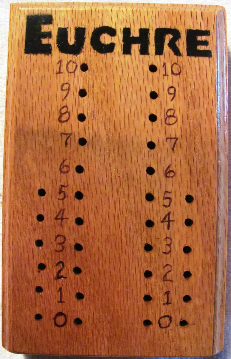 This euchre scorekeeper is crafted out of a block of scrap wood.  Golf tees are counters.