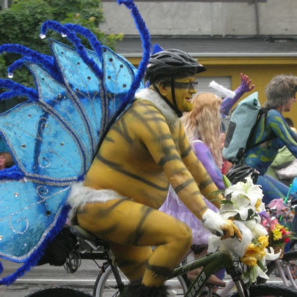 This bicycle rider has fantasy butterfly wings with fluffy trim.